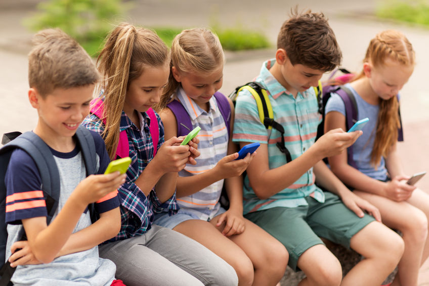 65551235 - primary education, friendship, childhood, technology and people concept - group of happy elementary school students with smartphones and backpacks sitting on bench outdoors